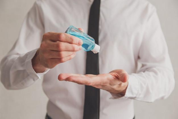 手の消毒剤ゲルディスペンサーのチューブを使用してオフィスワーカー。防腐剤、衛生学およびヘルスケアの概念