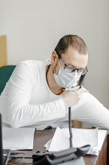 Офисный работник в маске сидит офис