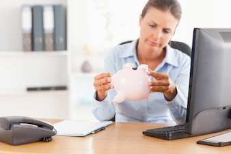 Office worker with an empty piggy bank in her office