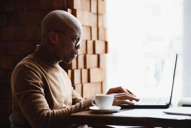 Офисный работник с кофе за столом, допоздна работая на ноутбуке