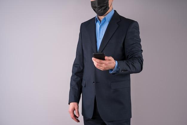 회색 벽에 보호 마스크에 휴대 전화로 회사원