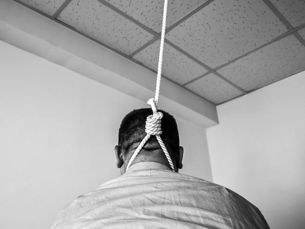 목에 올가미가 있는 회사원. 자살 개념입니다. 업무 스트레스로 인해 매달려 있습니다. 소진의 우울증. 끔찍한 생활 상황. 흑백 사진입니다.