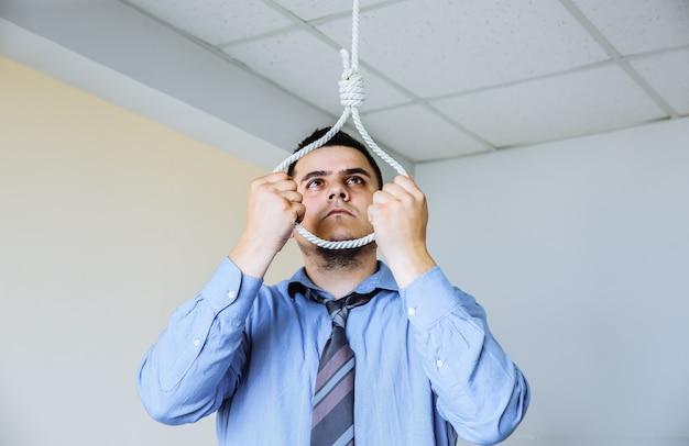 손에 올가미와 회사원입니다. 자살 개념입니다. 업무 스트레스로 인해 매달려 있습니다. 소진의 우울증. 끔찍한 생활 상황. 인생을 선택하는 남자.