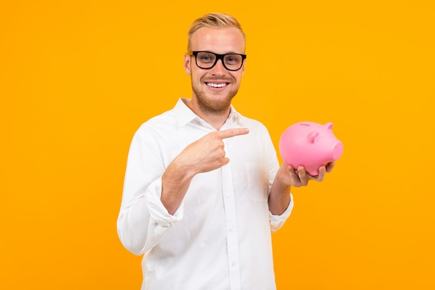 Office worker with a piggy bank money on a yellow wall