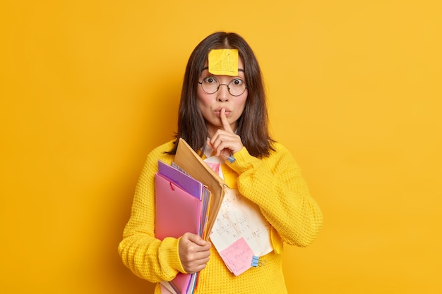 Office worker with sticker on forehead makes silence gesture holds folders wears round spectacles and jumper.