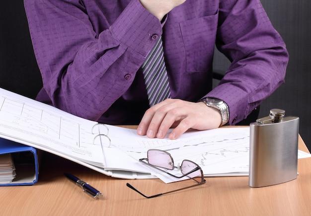 Офисный работник, работающий допоздна, испытывает стресс, на столе стоит фляжка с алкоголем