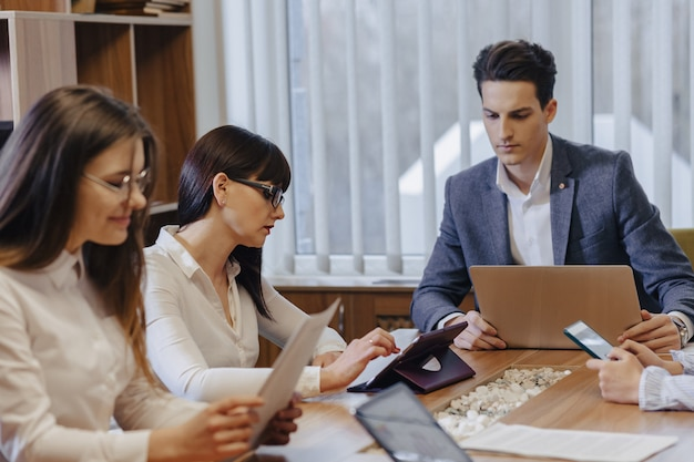 Office workers hold a meeting at one desk for laptops, tablets and papers
