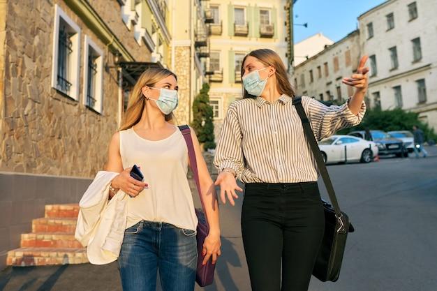 사무실 직원 두 명의 젊은 비즈니스 여성이 의료용 보호 마스크를 쓰고 도시 거리를 걷고 있습니다. 라이프 스타일, 전염병의 비즈니스, 전염병, 나쁜 생태