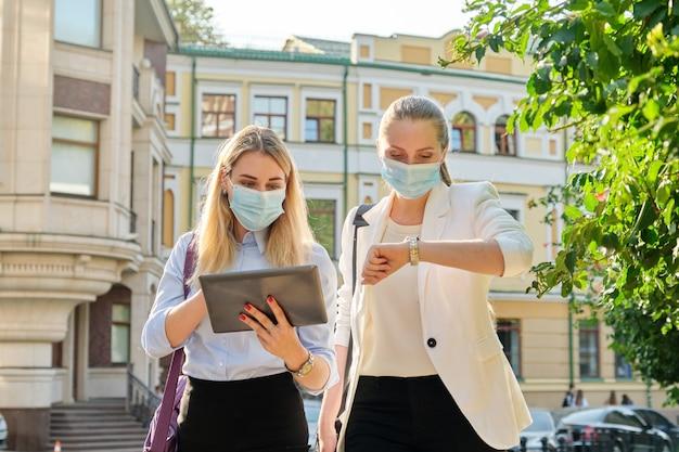 사무실 직원 2명의 젊은 비즈니스 여성이 디지털 태블릿, 도시 거리 배경으로 의료 보호 마스크를 착용하고 도시 거리를 걷고 있습니다. 라이프 스타일, 전염병의 비즈니스, 전염병