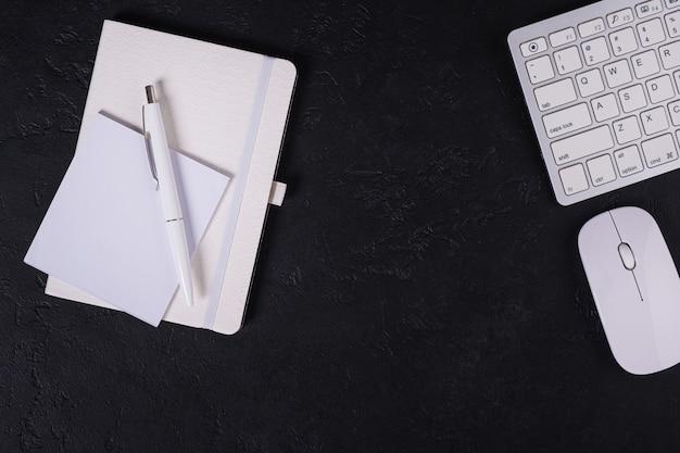 ノートとペンと仕事場の背景。黒いテーブルのキーボードとマウス。