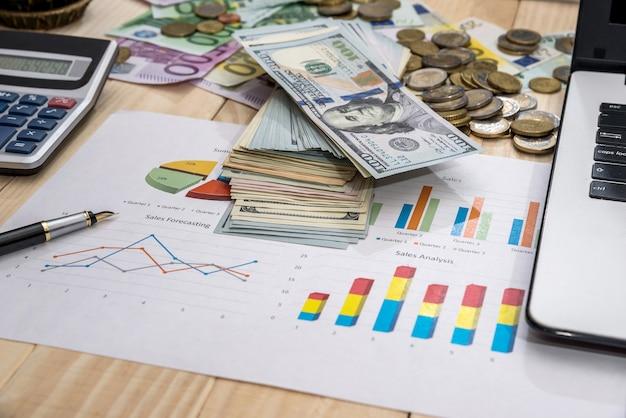 Офисное рабочее место, бизнес-диаграмма, ноутбук, ручка, доллар и калькулятор