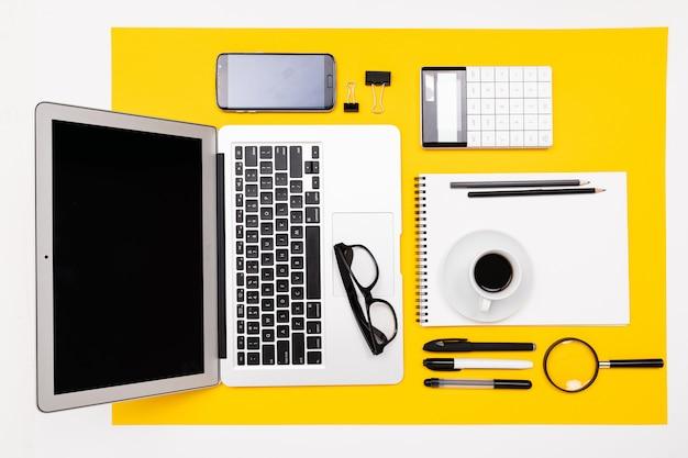 사무실 직장. 노트북, 메모장, 돋보기, 계산기 및 전화와 편지지 프레임 노란색 표면에 거짓말