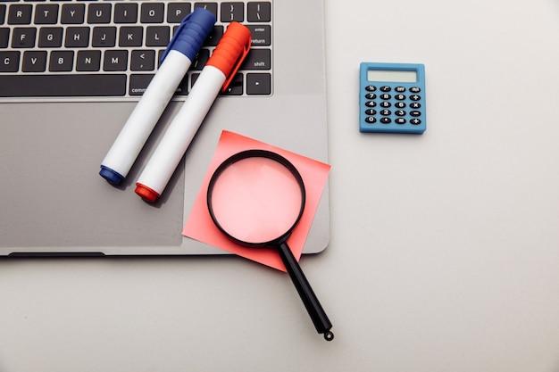 Офисное рабочее место. наклейки, калькулятор и увеличительное стекло. концепция бизнеса и финансов.