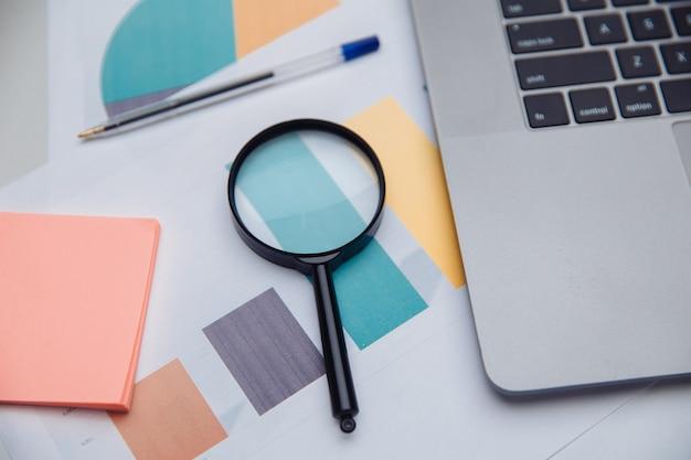 Офисное рабочее место. наклейки, диаграммы и увеличительное стекло. концепция бизнеса и финансов.