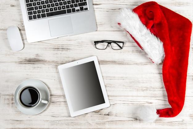 Офисное рабочее место с чашкой кофе и рождественскими украшениями. концепция деловых праздников