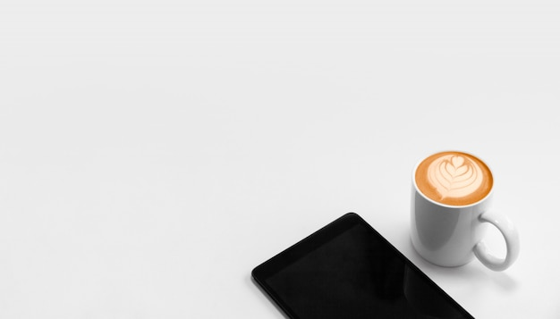 Office workplace with digital tablet and coffee cappuccino froth art