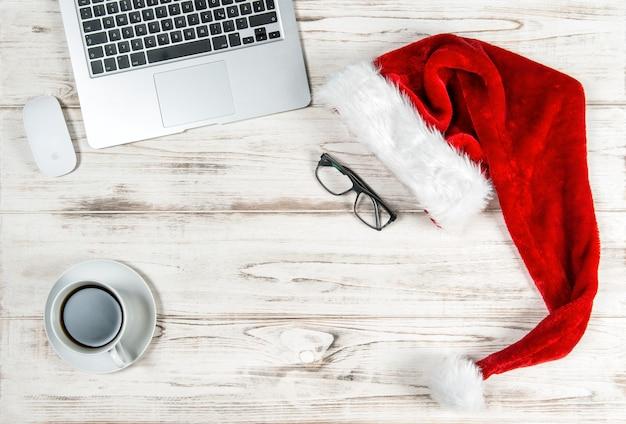Офисное рабочее место с клавиатуры портативного компьютера, кофе и рождественские украшения. концепция деловых праздников