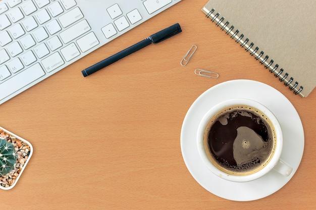 Офисное рабочее место с клавиатурой блокнот мышь кофе из чашки на деревянный стол. над светом