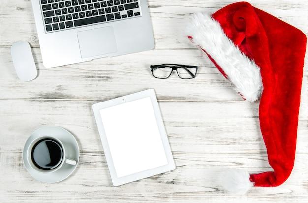 Офисное рабочее место с ноутбуком, кофе и рождественские украшения. концепция деловых праздников. скопируйте место для вашего текста