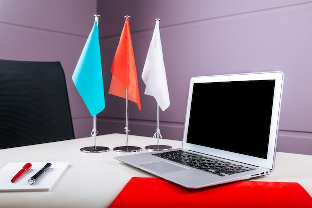 Office workplace with a laptop notebook pens flags