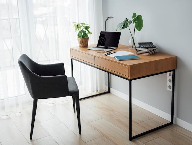 木製のテーブルの上のラップトップとオフィスの職場