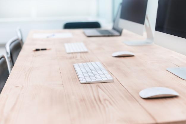 Офисное рабочее место с ноутбуками и компьютерами на деревянном столе.