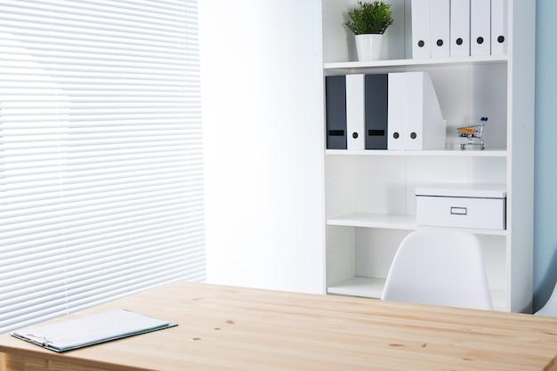 木製の机と本棚のあるオフィスの職場