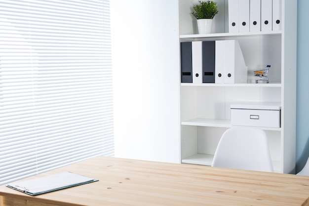 Office workplace with wooden desk and bookshelf