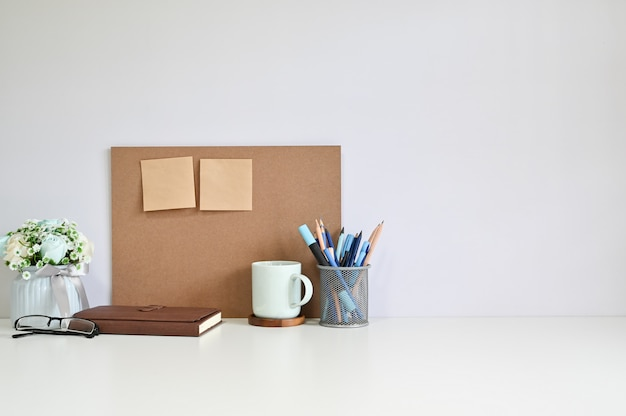 Office workspace board and sticky note, coffee with office supplies on table copy space.