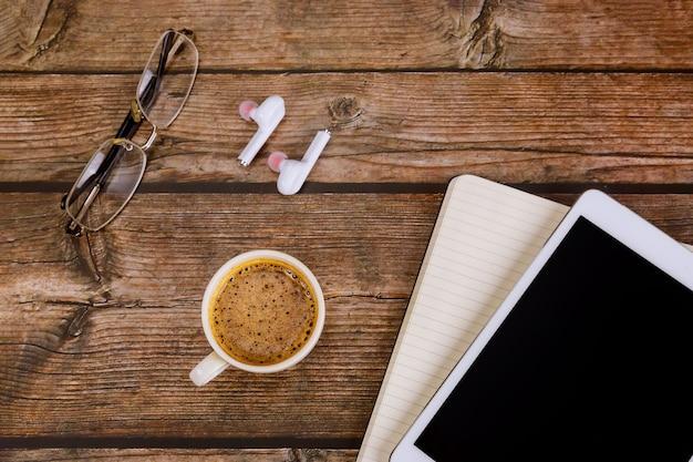 커피 에스프레소 컵, 노트북, 디지털 태블릿 무선 헤드폰이있는 사무실 작업 공간 책상 테이블