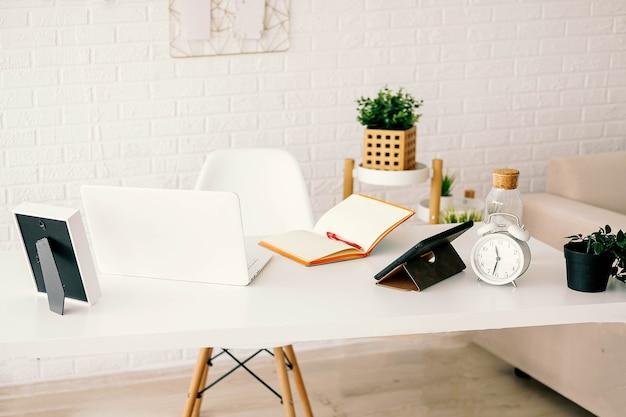 オフィスのワークスペースのモックアップラップトップ、ヘッドフォン、鉛筆、オフィスの机の上の植物の装飾。