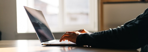 사무실 작업 공간입니다. 나무 테이블 위에 노트북 작업을 하는 남자가 있는 테이블