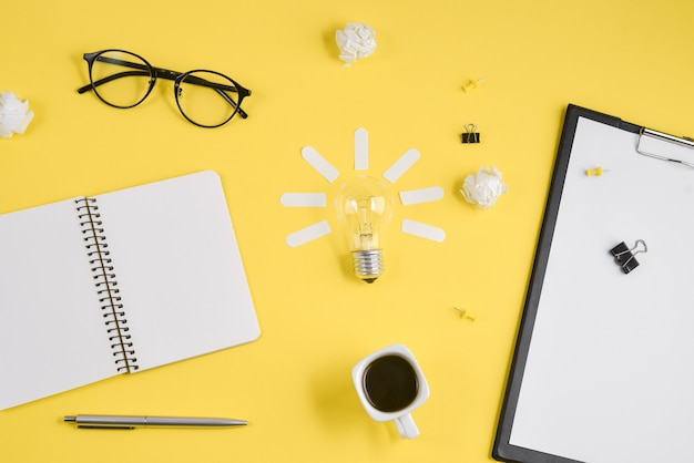 Office workspace with blank clip board, office supplies on yellow background.
