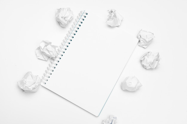 Office workspace with an empty notebook, crumpled paper