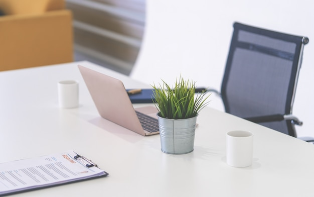 Офисное рабочее пространство с ноутбуком на белом офисном столе с объектами
