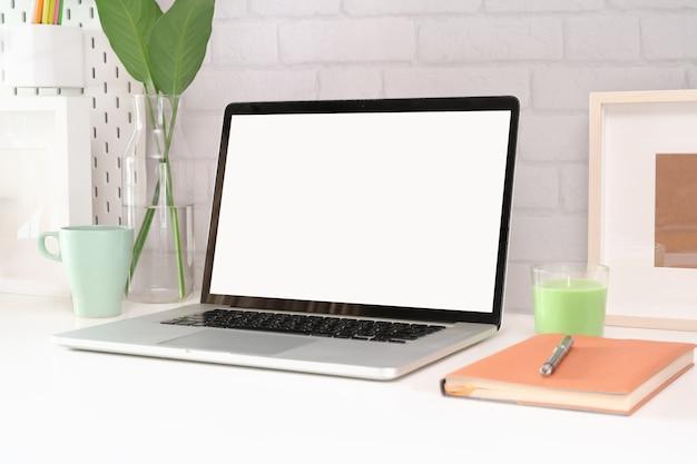 空白の画面のノートパソコンをモックアップでオフィスのワークスペース