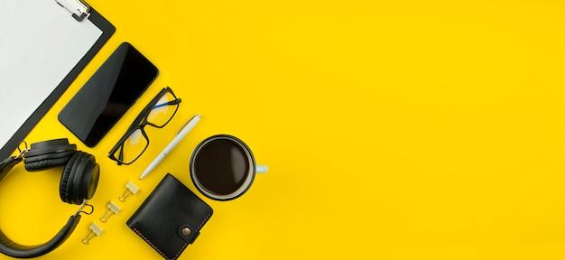 黄色の背景にスマートフォン、ヘッドフォン、officeアクセサリー。現代のライフスタイル。ビジネス。フラット横たわっていた。バナー。コピースペース。