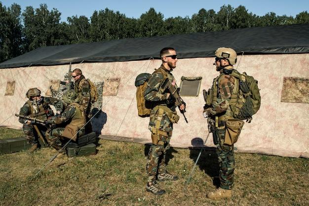 군사 작전을 위해 군인을 준비하고 군사 기지에서 그에게 조언을 하는 소총을 든 장교