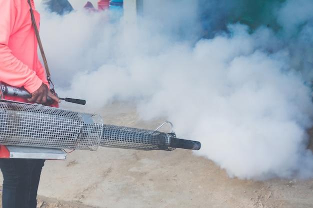 Офицеры впрыскивают средство для удаления комаров для удаления дыма и личинок