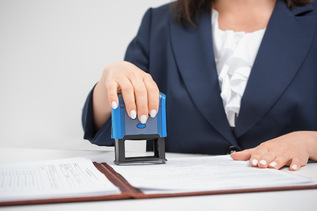 Official notary putting stamp on documents. in a blue jacket