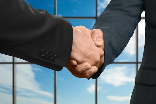 正式な服装の男性が握手します。青空の背景に握手。新しいパートナーを歓迎します。政党のメンバー。