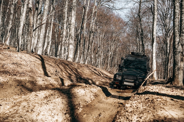 Offroad car driving through the forest road of mud