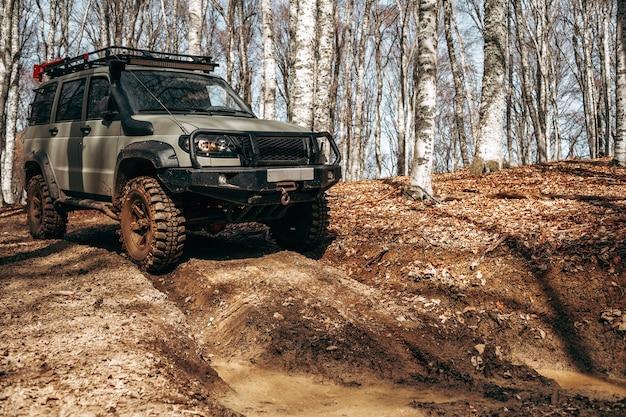 진흙의 숲길을 운전하는 오프로드 자동차