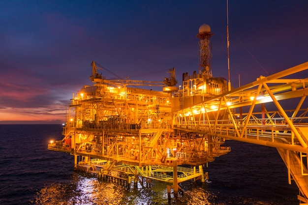 Offshore oil and gas rig platform with beautiful sunset time
