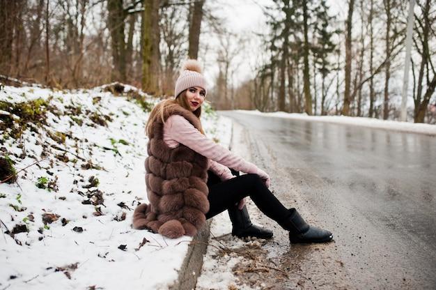 冬の日のボーダーofroadに座っている毛皮のコートと帽子のスタイリッシュな女性。