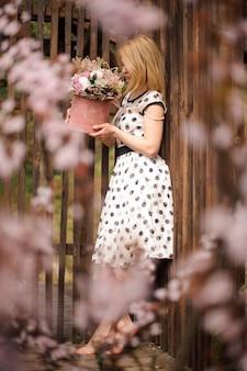 フェンスの近くにフラワーボックスを保持している水玉ドレスのサイドビューogブロンドの女性