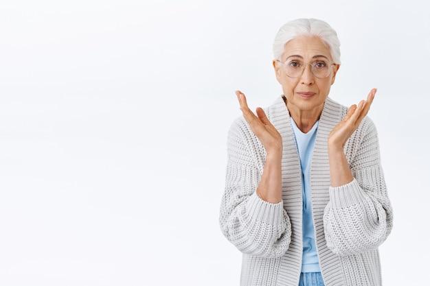 О, дорогая бабушка смотрит на ребенка, который так быстро вырос, поднимает руки возле щек от миловидности и прекрасной сцены, тронут и впечатлен, счастливо улыбается, стоит белая стена в очках