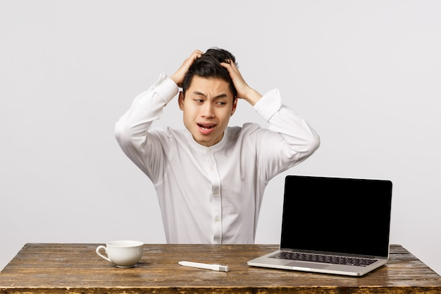 Oh god what have i done. puzzled and anxious, embarrassed young asian man in shirt, grab head shocked and distressed, staring laptop display, react to embarrassing video posted online