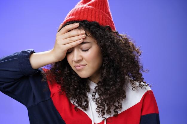 Oh dio perché io. ritratto di una ragazza carina incazzata e irritata con i capelli ricci che guarda in basso con rammarico e delusa facendo gesto di facepalm dal fastidio di essere infastidito da una domanda stupida.