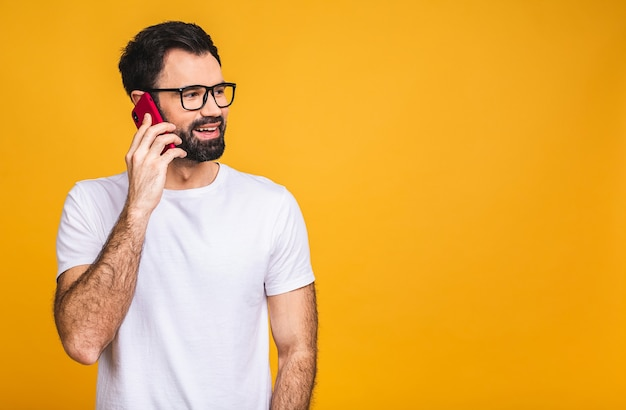 Oh, great news! smiling young bearded casual man in glasses talking on the mobile phone isolated over yellow background.